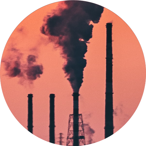 Four smokestacks billowing pollution into the air with an orange sky backdrop