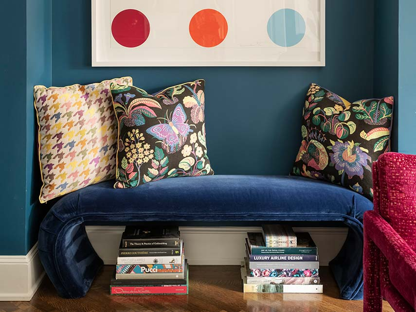 Blue bench with three colorful pillows and two stacks of books below