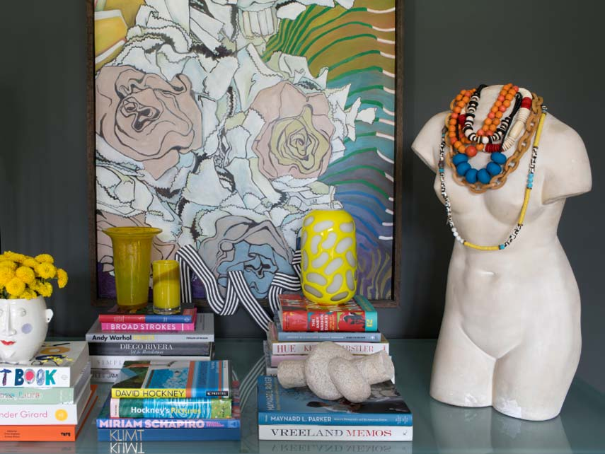 Stacks of books, wall art and a limbless sculpture adorned with colorful necklaces