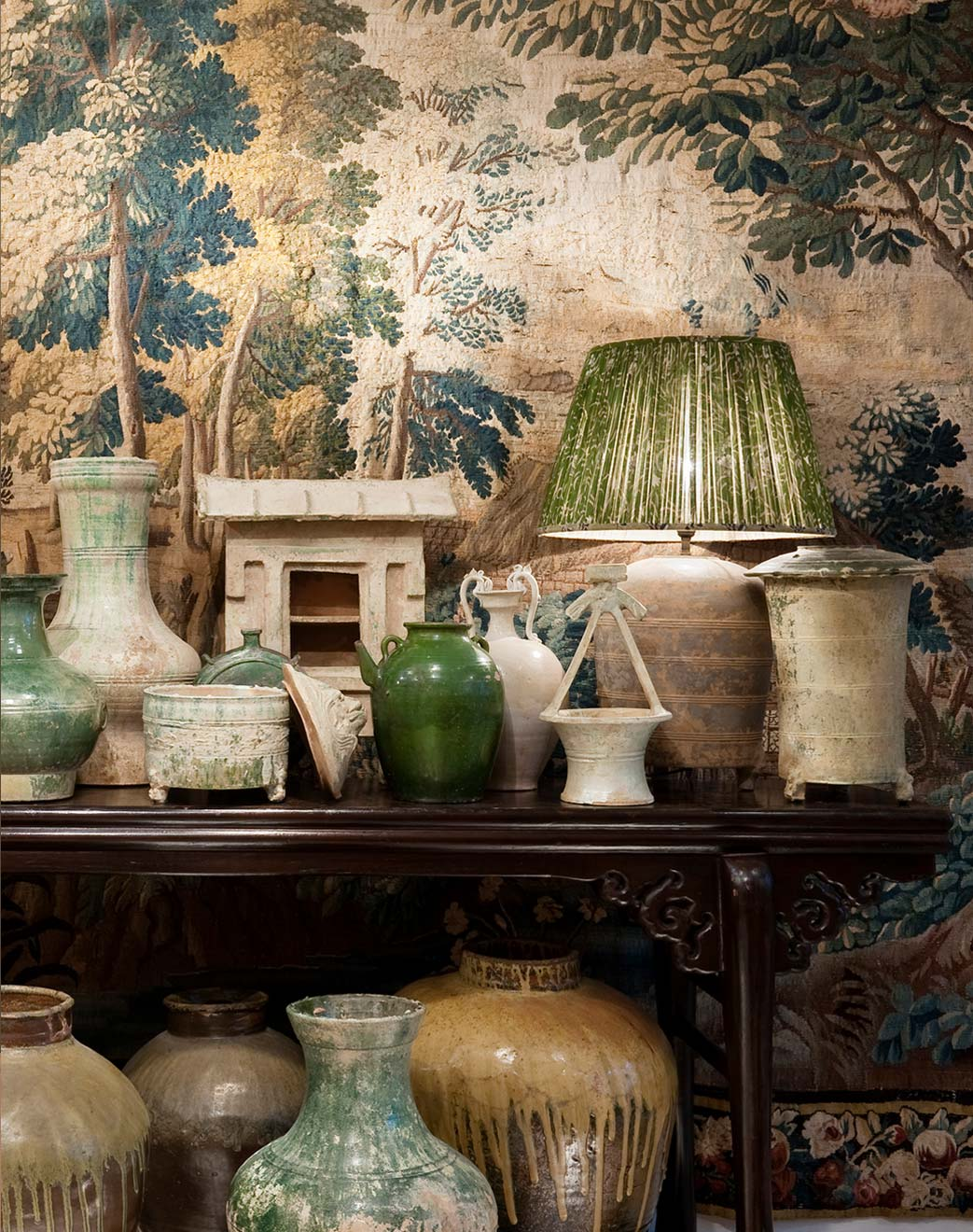 Lamp and other vintage decorative pieces in front of wall tapestry