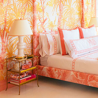 Side table next to an orange bed in an orange room