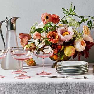 Dining table set with fine plates and glasses and an arrangement of flowers